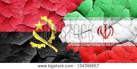 Angola flag with Iran flag on a grunge cracked wall