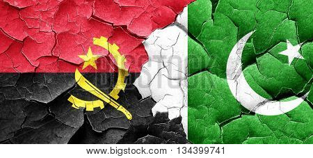 Angola flag with Pakistan flag on a grunge cracked wall