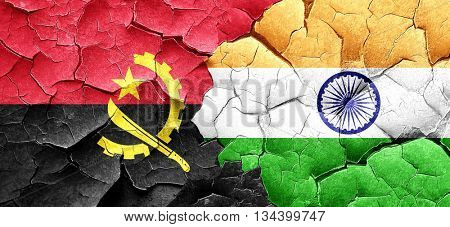Angola flag with India flag on a grunge cracked wall