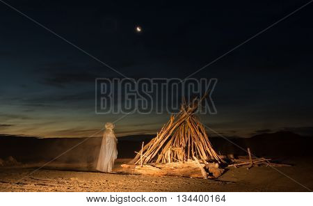 Jesus Christ standing by a drift wood shelter at night.