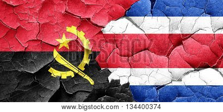 Angola flag with Costa Rica flag on a grunge cracked wall
