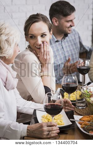 Grandmother and granddaughter talking during dinner at the table
