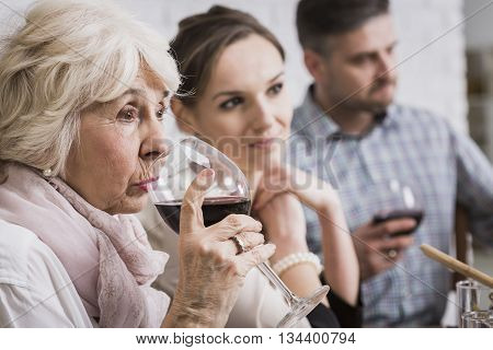 Senior woman drinking red wine at the table