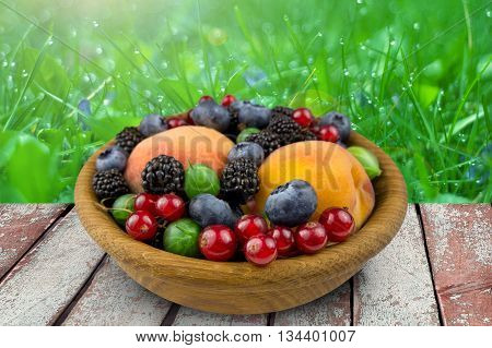 fruits and berries in a wooden plate gooseberry blackbery peach blueberry. on nature background