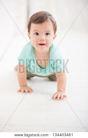crawling baby boy on living room floor and he smile to you caucasian child