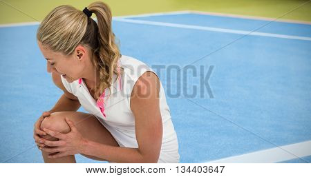 Injured athlete with tennis racket and tennis ball against composite image of tennis field