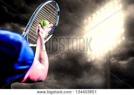 Tennis player holding a racquet ready to serve against spotlight in the sky