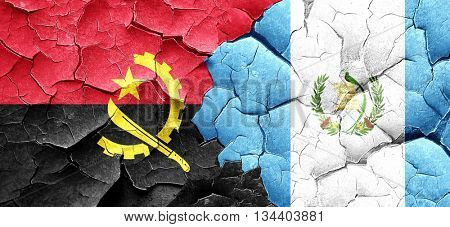 Angola flag with Guatemala flag on a grunge cracked wall