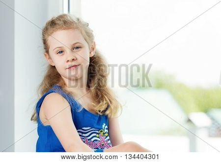 Adorable smiling little girl by the window.