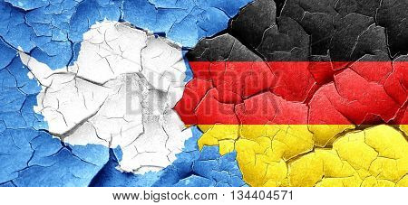 antarctica flag with Germany flag on a grunge cracked wall
