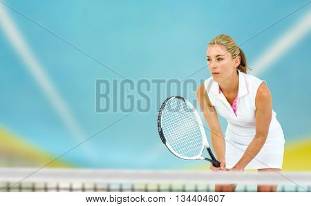 Athlete playing tennis with a racket against tracks on field on a sunny day