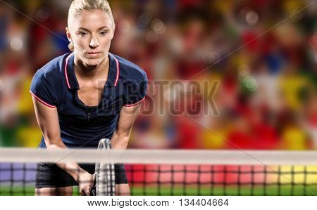 Tennis player playing tennis with a racket against blurry football pitch with crowd