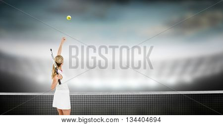 Athlete holding a tennis racquet ready to serve against large football stadium under cloudy sky
