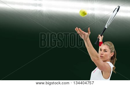 Athlete holding a tennis racquet ready to serve against spotlight