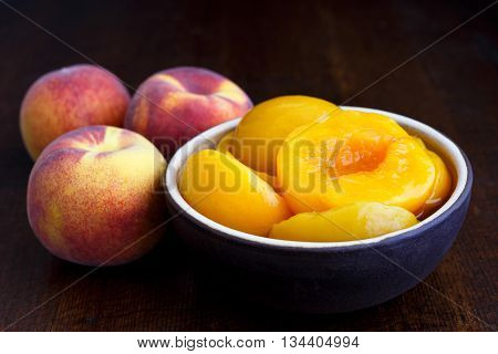 Canned Peach Halves In Bowl On Dark Background With Whole Fresh Peaches. In Perspective.