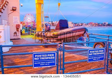 Santa Monica, CA, USA - January 11, 2016: Santa Monica California pier at sunset 66 sign. The roller coaster at the amusement park souvenirs