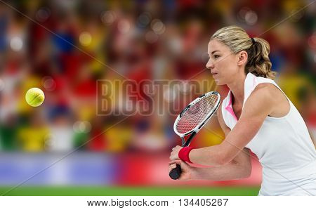 Athlete playing tennis with a racket against blurry football pitch with crowd