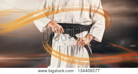 Mid section of fighter tightening karate belt against view of sport ground outdoor