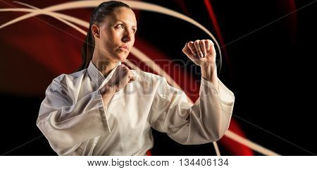 Female fighter performing karate stance against black background