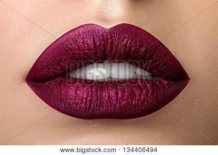 Close up view of beautiful woman lips with purple matt lipstick. Open mouth with white teeth. Cosmetology drugstore or fashion makeup concept. Beauty studio shot. Passionate kiss