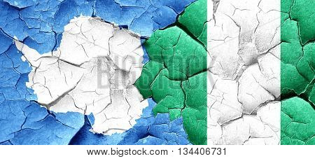 antarctica flag with Nigeria flag on a grunge cracked wall