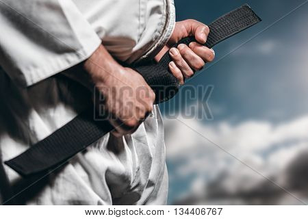 Fighter tightening karate belt against sky with clouds