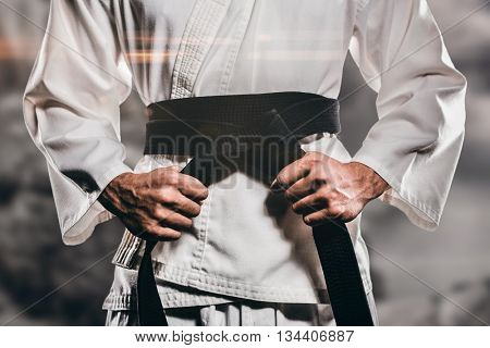 Fighter tightening karate belt against rock crashing down from cliff