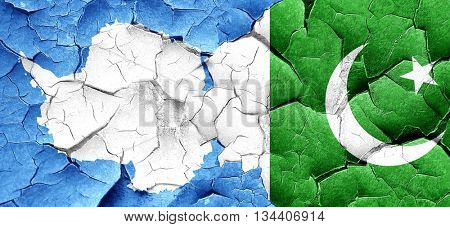 antarctica flag with Pakistan flag on a grunge cracked wall