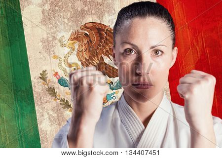 Female fighter performing karate stance against mexico flag in grunge effect