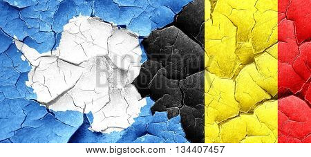 antarctica flag with Belgium flag on a grunge cracked wall