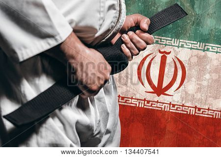 Fighter tightening karate belt against iran flag in grunge effect