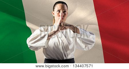 Female fighter performing hand salute against digitally generated italy national flag