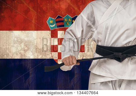 Fighter tightening karate belt against croatia flag in grunge effect