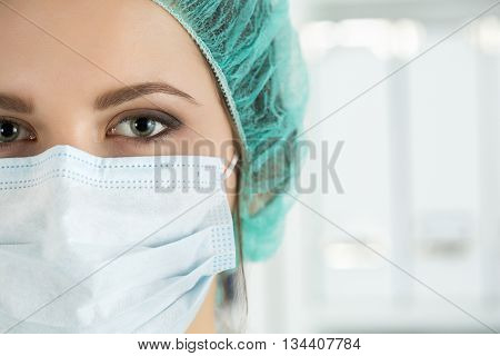 Close-up portrait of young female surgeon doctor or intern wearing protective mask and hat. Healthcare medical education emergency medical service surgery or veterinary concept