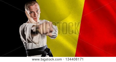 Fighter performing karate stance against digitally generated belgium national flag