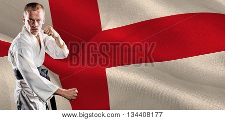 Fighter performing karate stance against digitally generated england national flag
