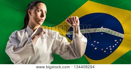 Female fighter performing karate stance against digitally generated brazil national flag