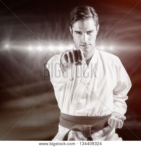Portrait of fighter performing karate stance against spotlights