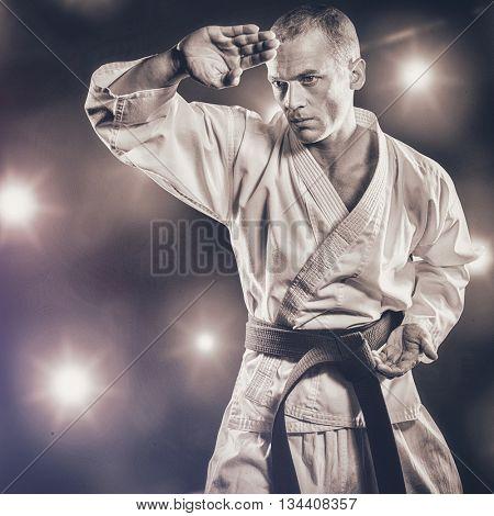 Fighter performing karate stance against composite image of orange spotlight