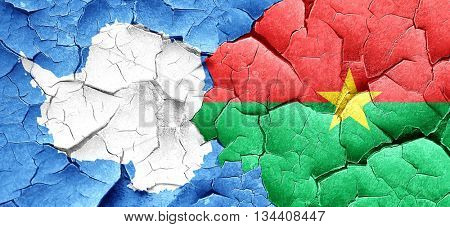 antarctica flag with Burkina Faso flag on a grunge cracked wall