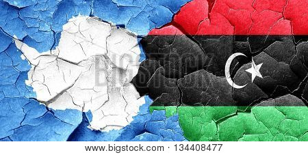 antarctica flag with Libya flag on a grunge cracked wall