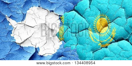 antarctica flag with Kazakhstan flag on a grunge cracked wall
