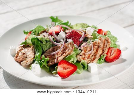 Portion of steaks with strawberry and feta cheese. Front view on white plate with meat steaks with strawberries, greens and feta on white background.