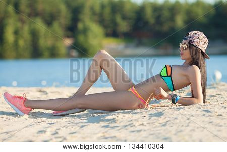 Attractive sexy tanned woman on the beach. Summer vacation. Hot woman in pink sneakers and color swimsuit. Blurred background.