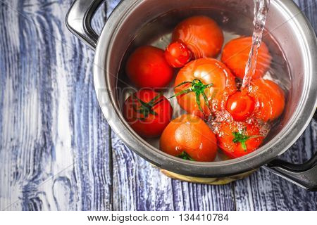Stream of water the tomatoes in a pot on a blue and white boards horizontal