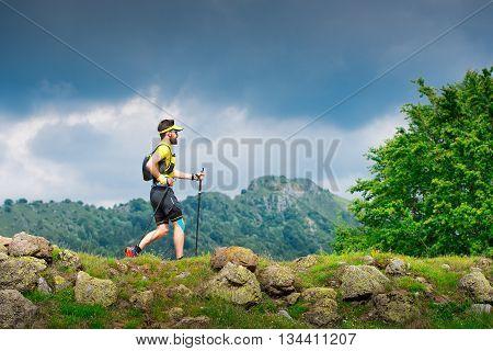 Male Athlete Practice Nordic Walking On Mountain Path