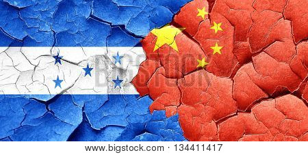 Honduras flag with China flag on a grunge cracked wall