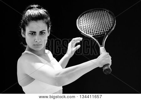 Portrait of confident female tennis player with racquet over black background