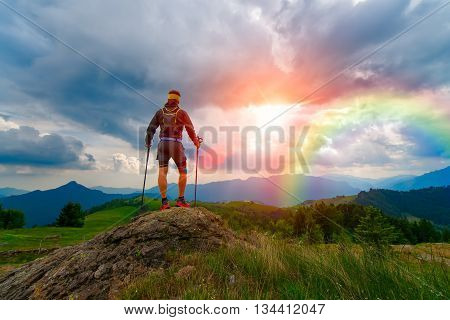 Man In The Mountains At Sunset With Rainbow