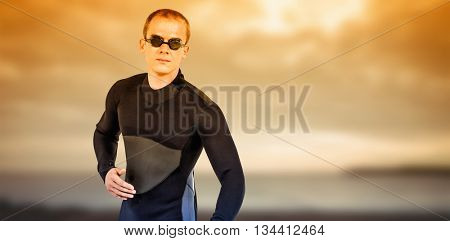 Swimmer in wetsuit and swimming goggles against grey sky over ocean